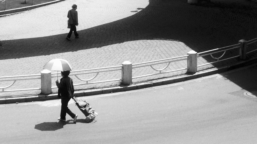High Angle View Of Person With Luggage Walking On Street
