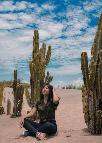 Full length of smiling woman sitting by cactus in desert