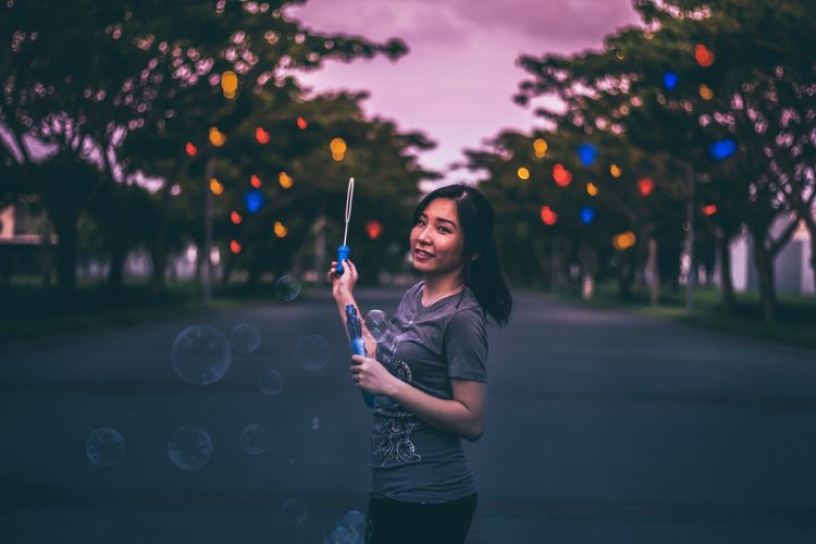 Portrait of woman playing with bubble wand on street at dusk