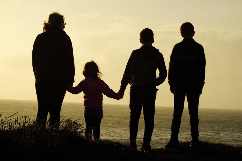 Silhouette woman with children standing on cliff by sea at sunset