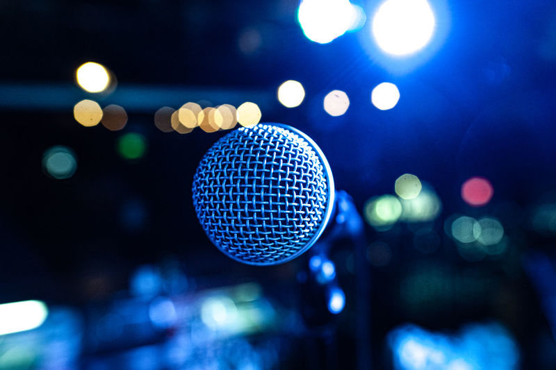 The vocalist's microphone stands on stage in the light of multicolored spotlights