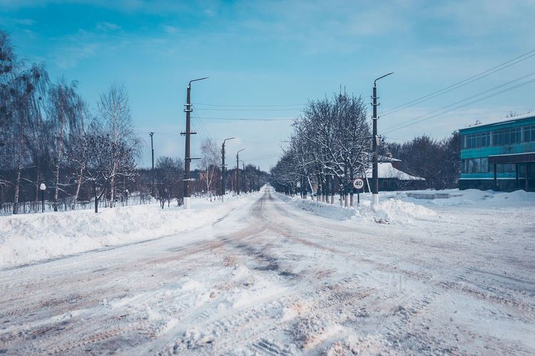 Snow covered road against sky