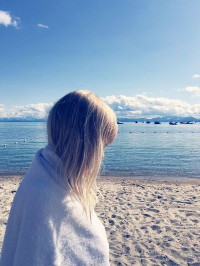 Side View Of Girl Wrapped In Towel At Beach By Lake Tahoe Against Sky