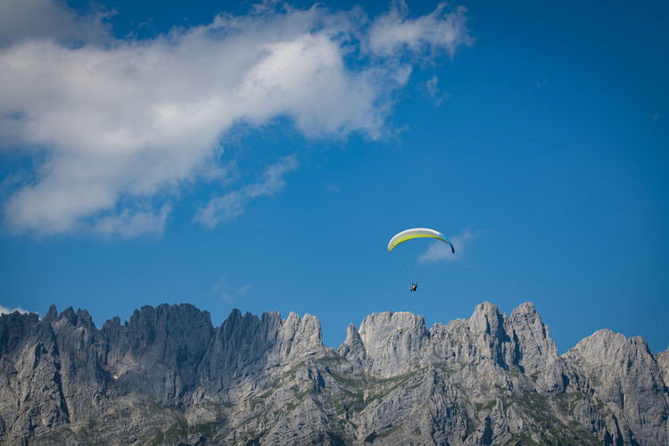 Paraglider Paragliding Adventure Extreme Sports Mountain Sky Parachute Beauty In Nature Flying Mid-air Cloud - Sky Day Sport Nature Low Angle View Mountain Range Scenics - Nature Leisure Activity Tranquil Scene Unrecognizable Person Non-urban Scene Freedom Outdoors Mountain Peak Formation