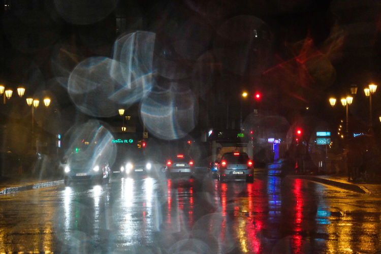 Cars on wet street during rainy season at night