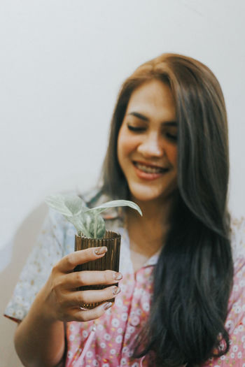 Portrait of a smiling young woman holding glass