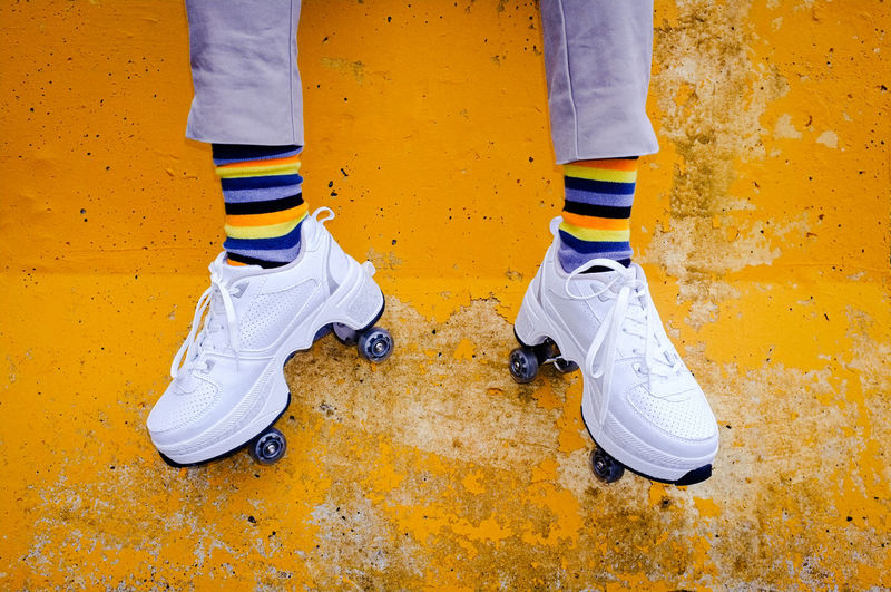 Low section of girl with roller skates against yellow wall