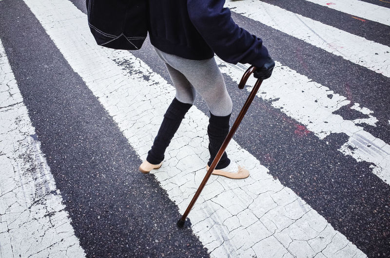 Single person walking across the street while using a cane walking stick in new york city