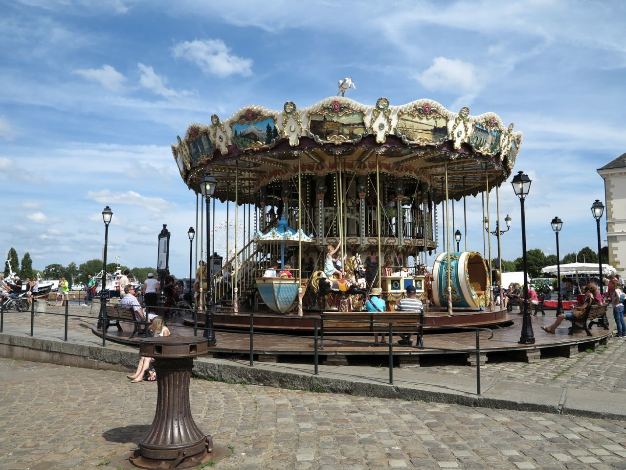 amusement park, arts culture and entertainment, carousel, sky, leisure activity, enjoyment, day, outdoors, amusement park ride, men, sitting, carousel horses, large group of people, merry-go-round, nature, people