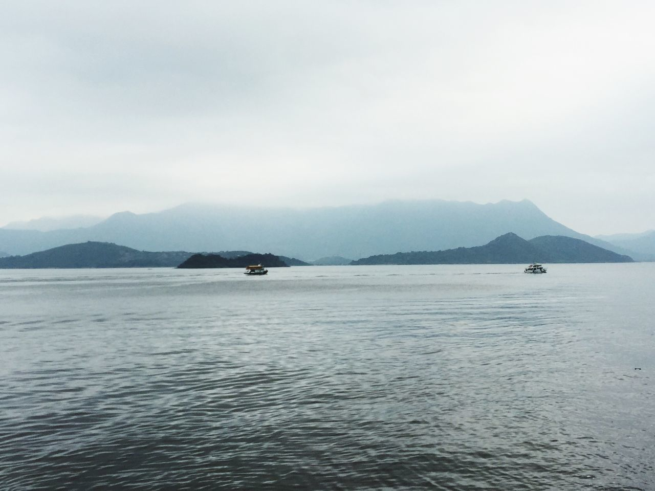 View Of Sea With Mountains In Background