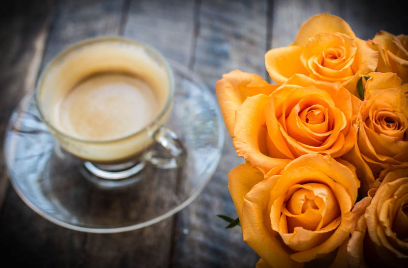 Orange rose on wooden desk with half of coffee in the background Beautiful Brown Check This Out Close-up Coffe Day Design Food Food And Drink Freshness Half Of Cu Indoors  Latte No People Orange Rosé Table