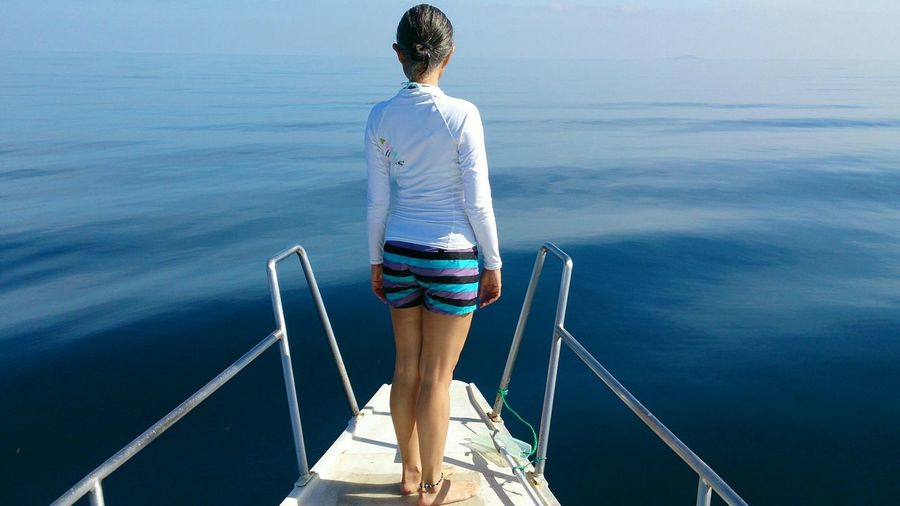 Full length rear view of woman standing on diving platform