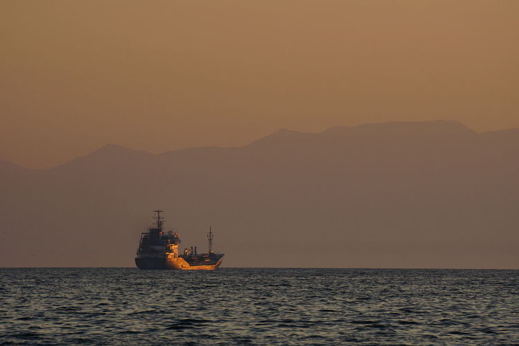 Silhouette ship sailing on sea against clear sky during sunset