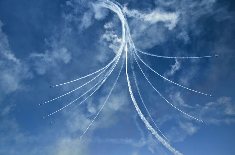 Low angle view of air show in blue sky