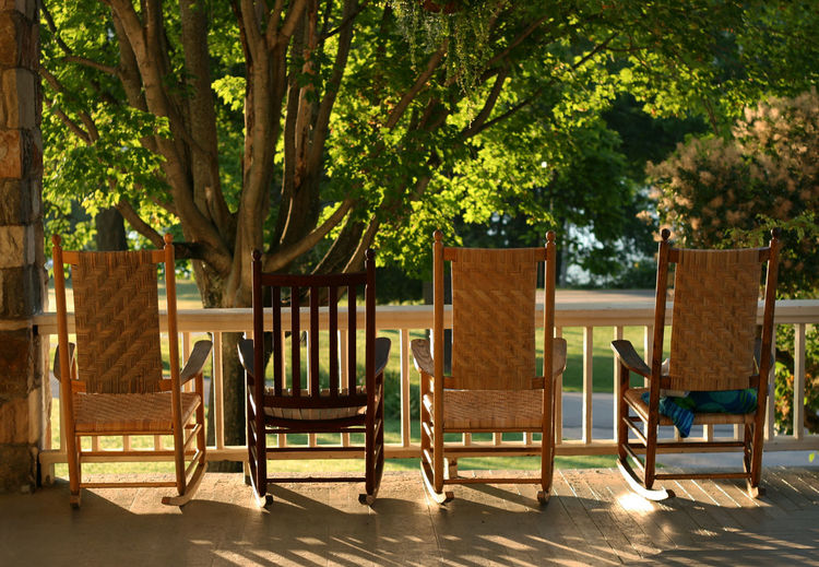 Empty wooden chairs against trees at porch