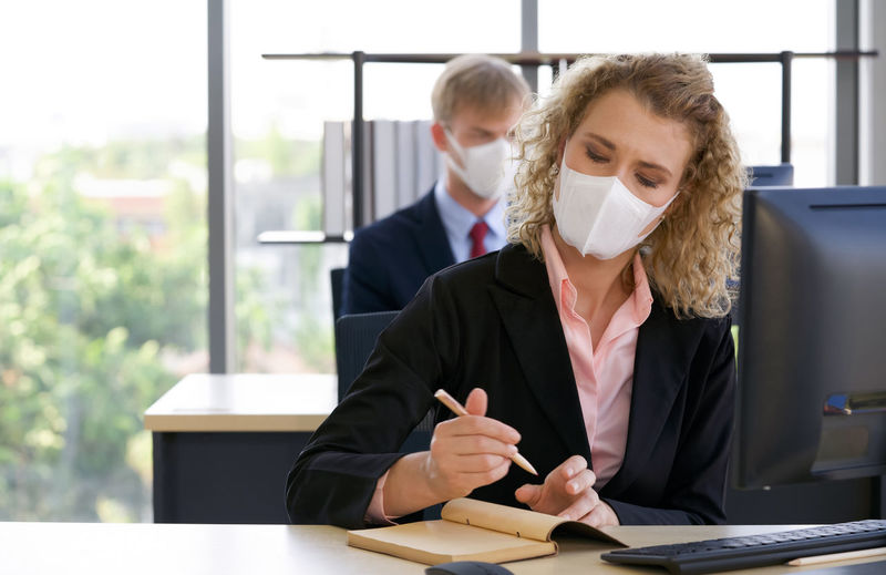 Businesswoman wearing mask writing in diary