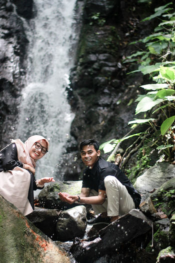 Portrait of couple sitting on rocks against waterfall