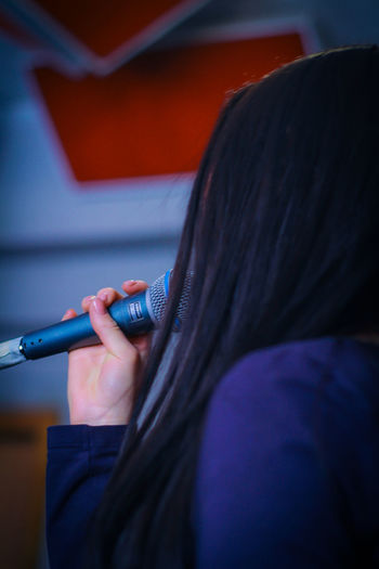 Close-up of woman holding microphone