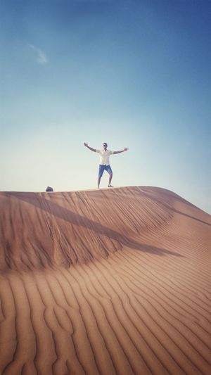 Mid distance view of man with arms outstretched standing on sand dune against blue sky