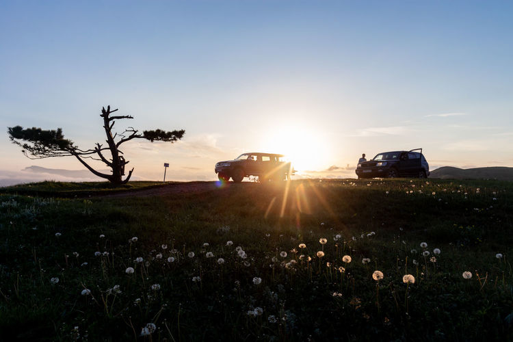 Sky Plant Transportation Land Vehicle Mode Of Transportation Field Sunlight Nature Beauty In Nature Land Sun Landscape Sunset Lens Flare No People Sunbeam Environment Scenics - Nature Growth Motor Vehicle Outdoors Bright