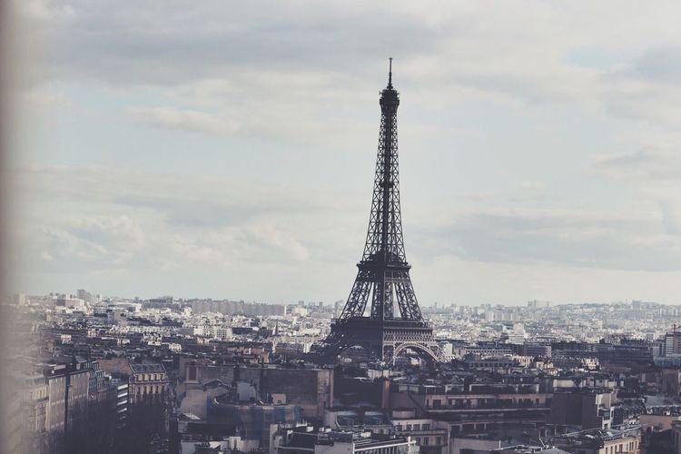 Eiffel tower against cloudy sky