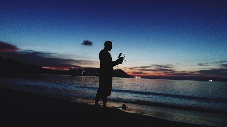 Silhouette Man Holding Remote Control Of Drone At Beach During Sunset