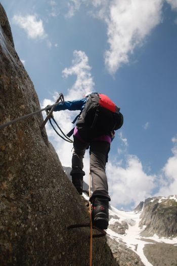Low Angle View Of Boy Climbing On Mountain Against Sky