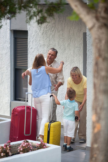 Mature Couple Greeting Grandson With Daughter At Entrance Of House