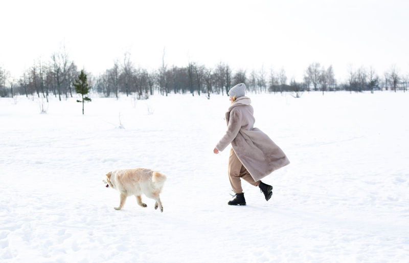 Full length of a man walking on snow covered field