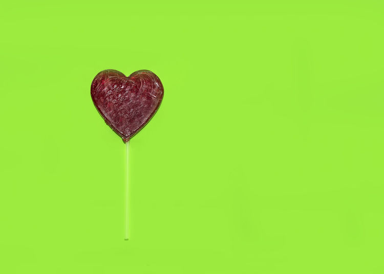 Red Heart lollipop on green background with copy space. Love concept. Indoors  No People Studio Shot Backgrounds Copy Space Wallpapaer Heart Shape Lollipop Red In Love Romance Romantic Celebrate Celebration Vintage Object Colorful Fun Tasty Delicious Green Isolated Sticking Out Tongue Sweet