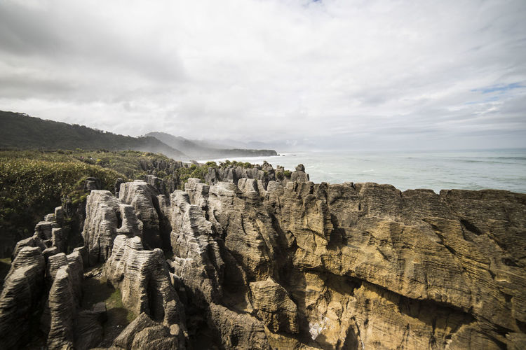 Famous rock formation in Punakaiki, New Zealand Pancake Rocks Punakaiki, New Zealand WestCoast Beauty In Nature Cliff Cloud - Sky Geology Land Landscape Mountain Nature New Zealand Non-urban Scene Ocean Outdoors Rock Rock - Object Rock Formation Scenics - Nature Sea Sky Tranquil Scene Tranquility Travel Water