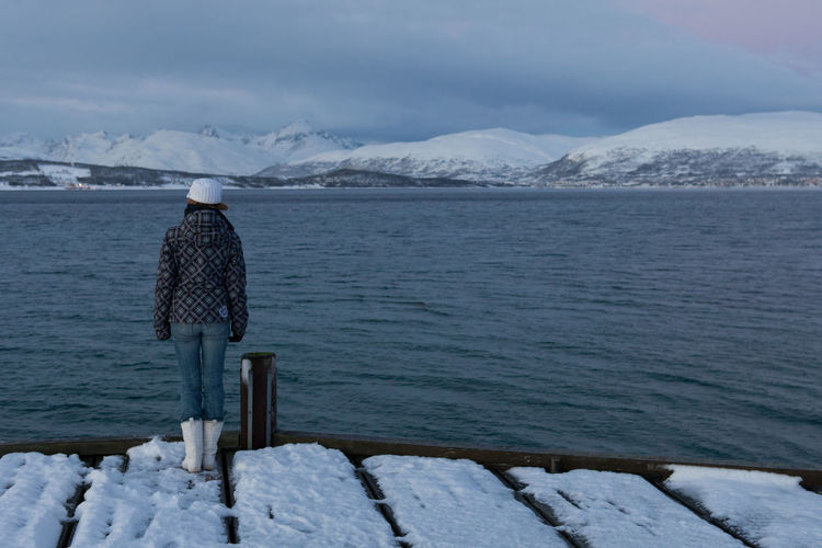 Rear view of woman standing on jetty against sky during winter