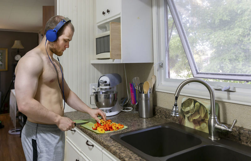 Side view of shirtless young man chopping food on kitchen counter at home