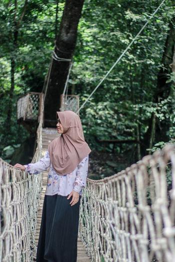 Woman wearing hijab standing on footbridge in forest