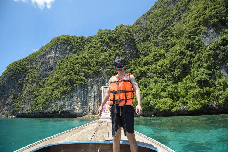 Portrait of man wearing snorkel standing on boat on mountain against sky