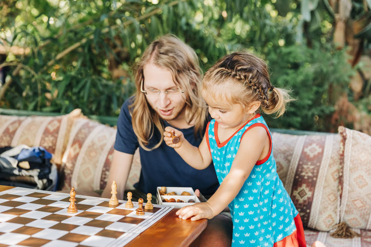 Father and daughter playing chess on table