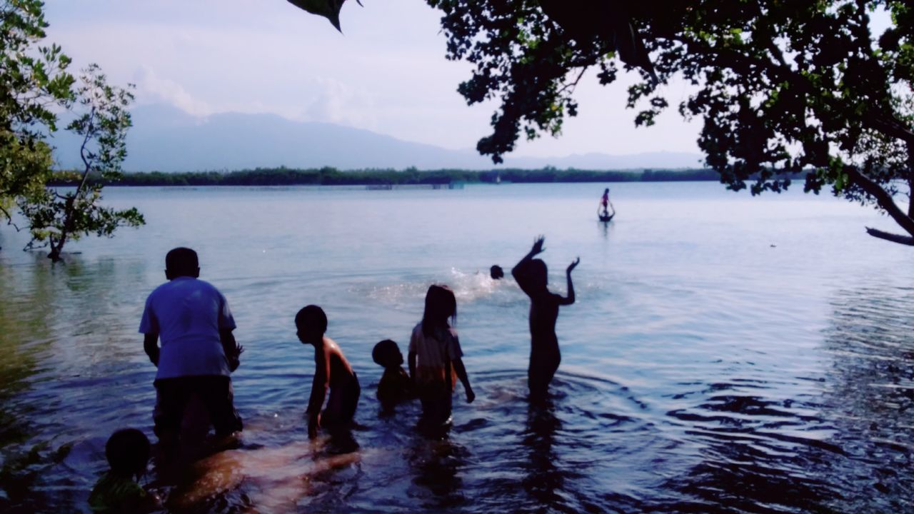 water, tree, group of people, sky, nature, leisure activity, plant, men, real people, beauty in nature, sea, day, outdoors, enjoyment, lifestyles, women, vacations, beach