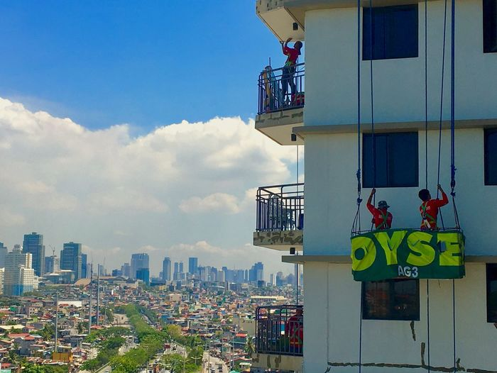 Workers repaint the exterior of a condominium in Taguig, Metro Manila. Architecture Building Exterior Built Structure City Sky Day Cloud - Sky Real People Residential Building Outdoors Cityscape Men Skyscraper People Painter Repainting Workers Philippines Manila Taguig Condominium