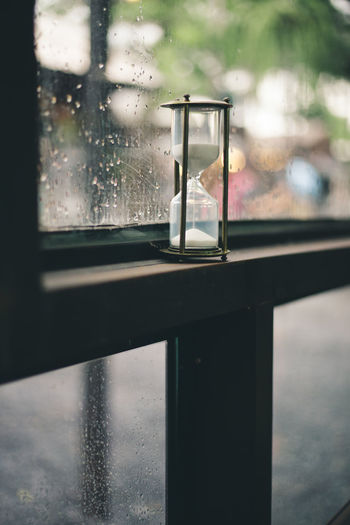 Close-up of hourglass by wet window in rainy season