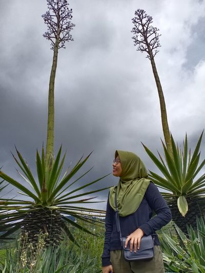 Woman wearing hijab standing amidst plants against cloudy sky