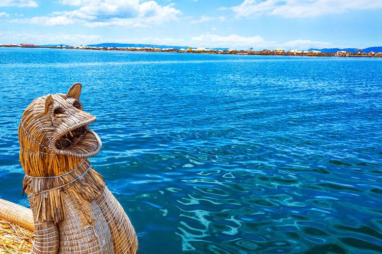 Reed boat at Uros floating islands on Lake Titicaca near Puno, Peru America Andes Boat Destination Floating Inca Lake Landscape Latin Native Nature Peru Peruvian Puno Puno, Perú Reed Scenic Sky Titicaca Titicaca Lake Totora Travel Uros Uros Island Water
