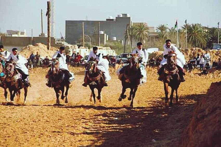 Animal Riding Horseback Riding Outdoors People Desert Domestic Animals Adult Day Horse Racing Sports Race Animal Themes Adults Only Sky Mammal