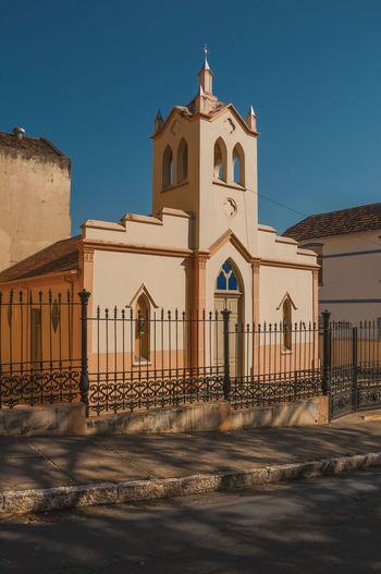 Church by building against clear blue sky