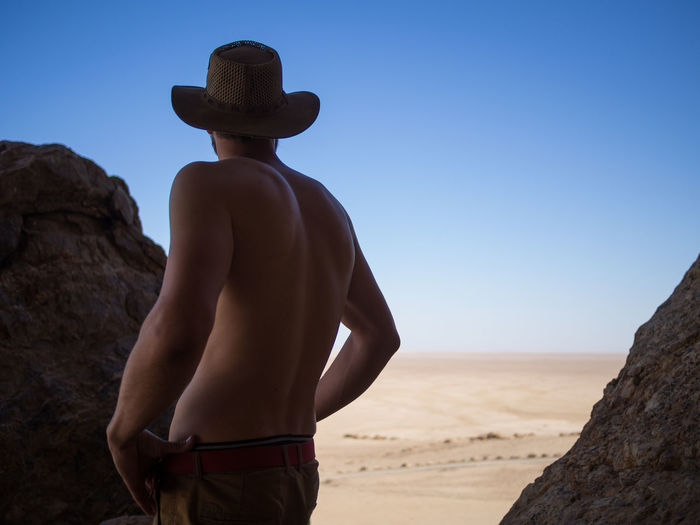 Rear view of shirtless man standing at rock against clear sky, namib naukluft national park, namibia