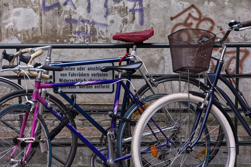 Bicycle parked by wall in city