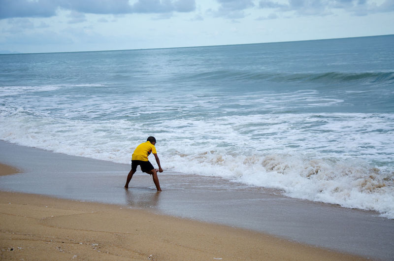 Rear view of person on sea shore against sky