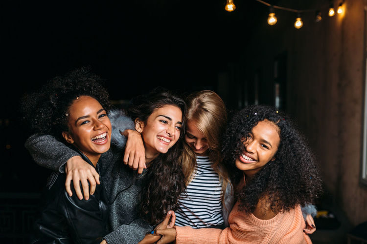 Happy female friends enjoying at night