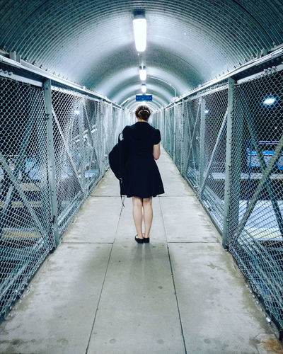 A woman standing still in a tunnel. Alone Lonely Peace Quiet Architecture Backpack Built Structure Casual Clothing Ceiling Diminishing Perspective Direction Full Length Illuminated Lifestyles Light One Person Real People Rear View Solitude Standing The Way Forward Traveler Tunnel Women