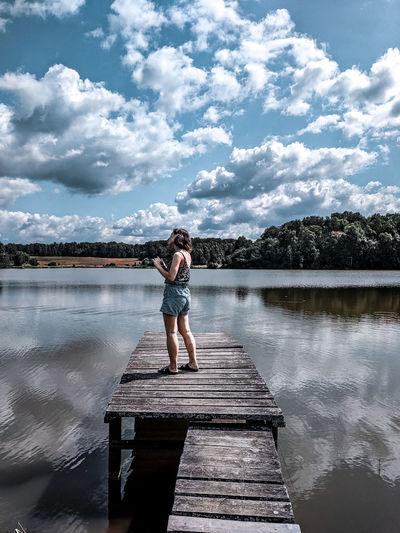 Full length of man standing on pier over lake against sky