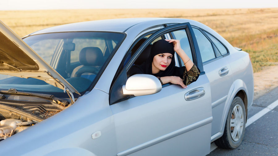 Smiling woman looking away while sitting in car